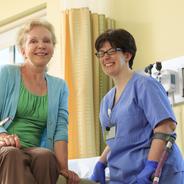 """""""Nurse with Cerebral Palsy consulting with a patient in a clinic"""" stock image"""