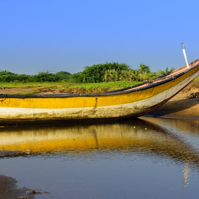 """Local colorful fishing boat anchored in the shallow water"" stock image"
