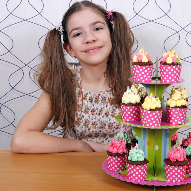 """""""Happy little girl with muffins dessert"""" stock image"""
