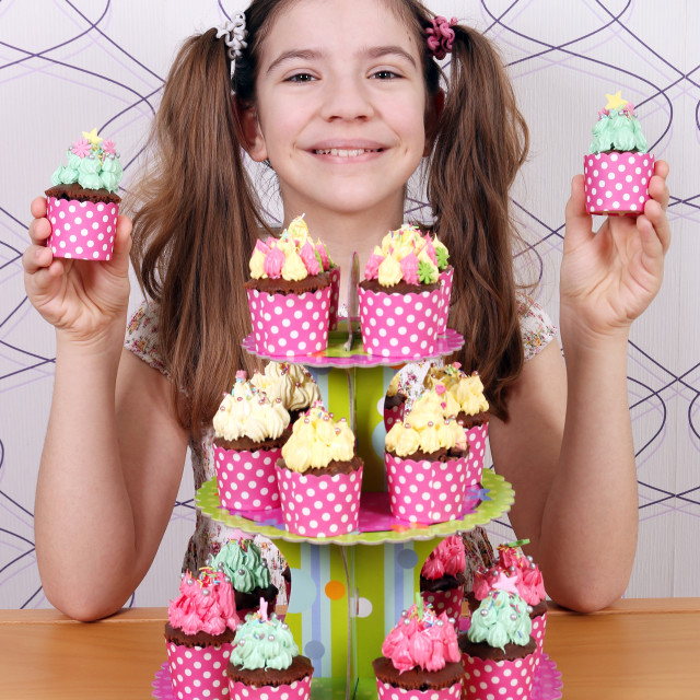"""""""Happy little girl with sweet muffins dessert"""" stock image"""