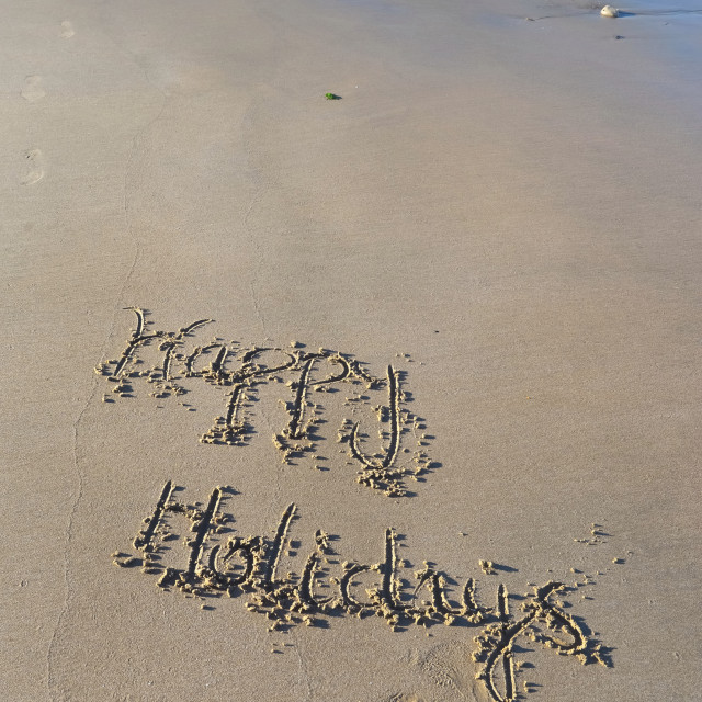 """happy holiday hand written on the sand in the beach"" stock image"