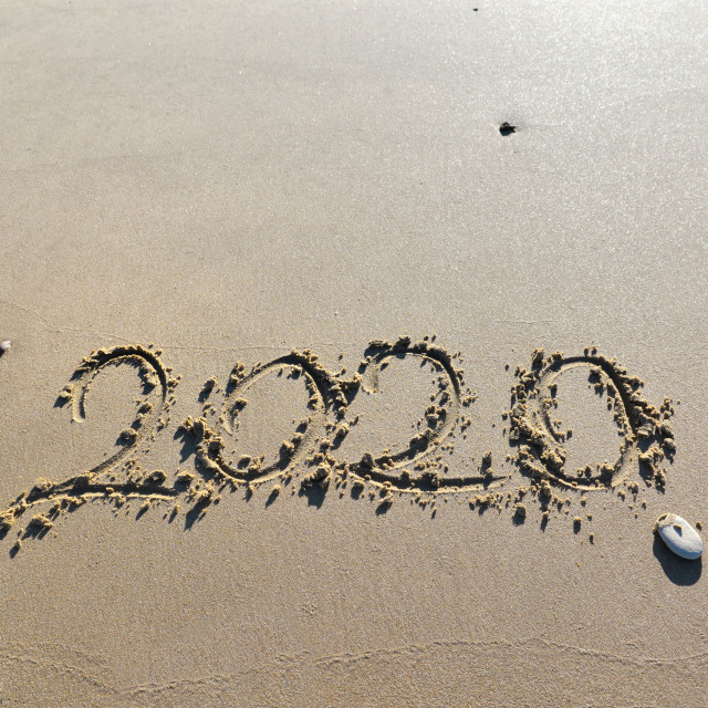 """""""year 2020 hand writting with a pebble on the sand to the beach"""" stock image"""