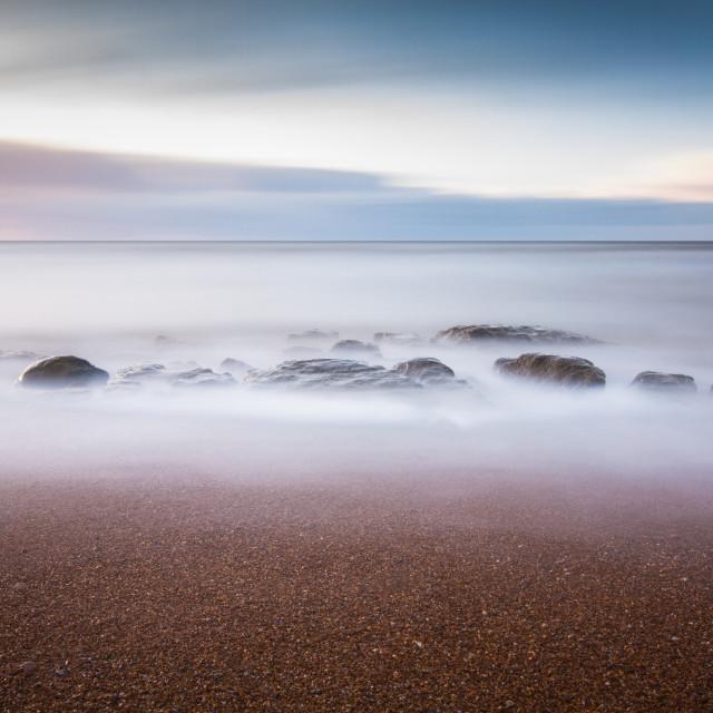 """long exposure of rocks on the beach"" stock image"