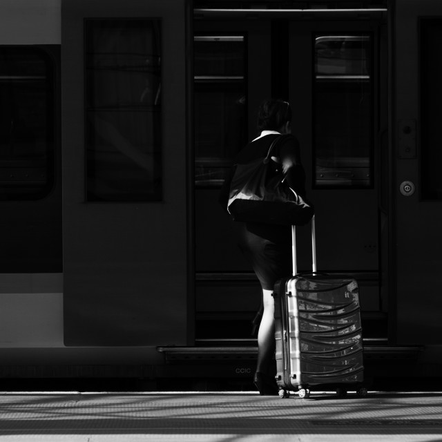 """A business woman with a suitcase boarding a train"" stock image"