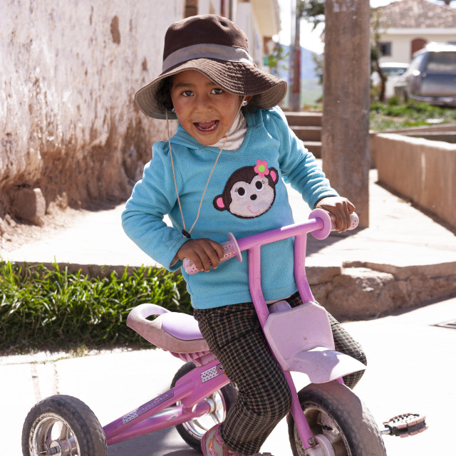 """Peruvian kid on her tricycle"" stock image"