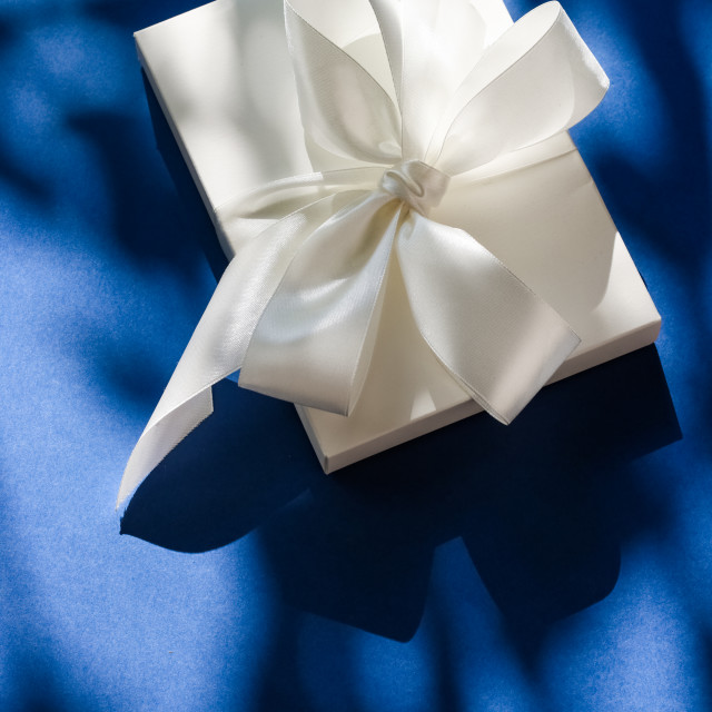 """""""Luxury holiday white gift box with silk ribbon and bow on blue background,..."""" stock image"""