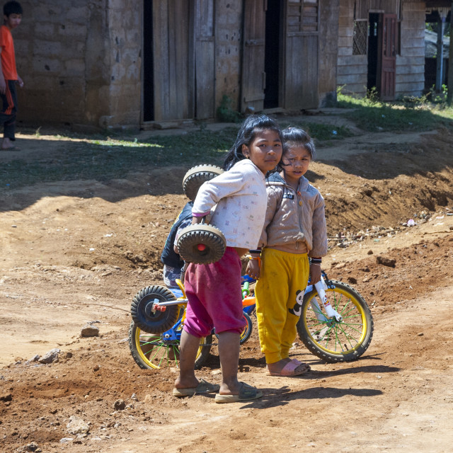 """""""Girls playing with bikes, Laos"""" stock image"""