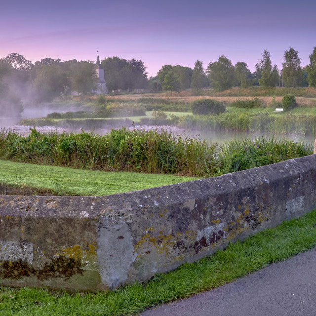 """Misty dawn light on Stoke Charity village pond and St Michael's"" stock image"