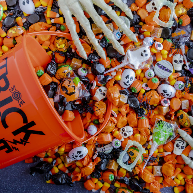 """""""Halloween candy spilling out of orange trick or treat bucket"""" stock image"""