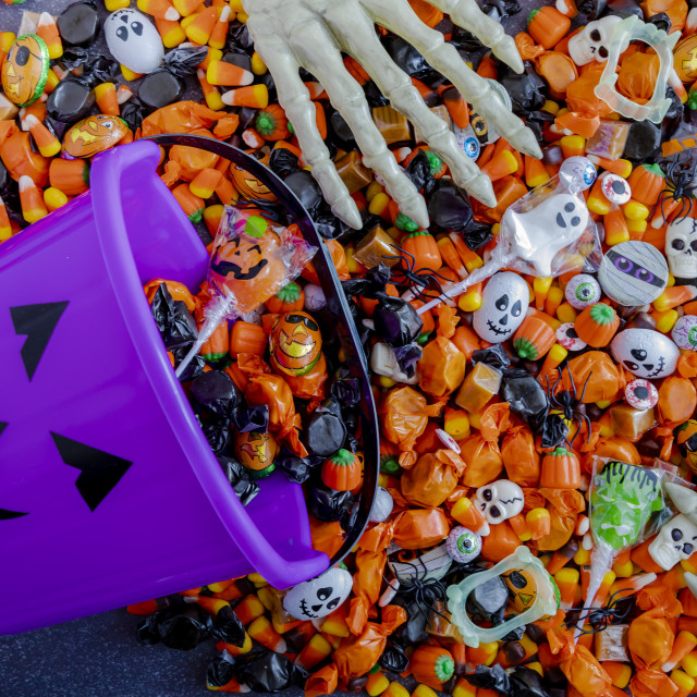 """""""Halloween candy spilling out of purple pumpkin bucket"""" stock image"""