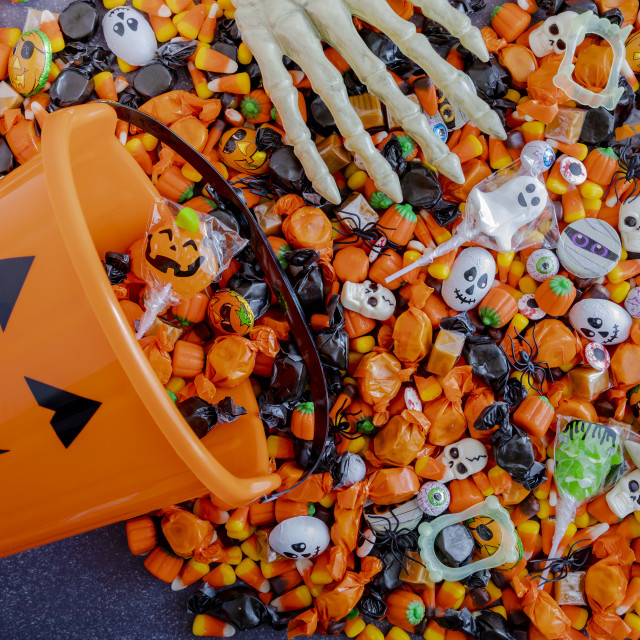 """""""Halloween candy spilling out of orange pumpkin bucket"""" stock image"""