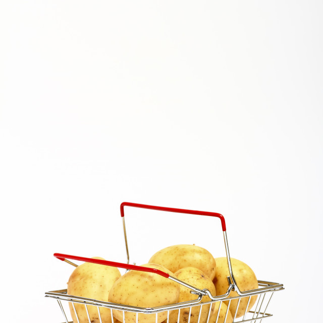 """Miniature shopping basket filled with potatoes isolated on a white background with space for copy"" stock image"