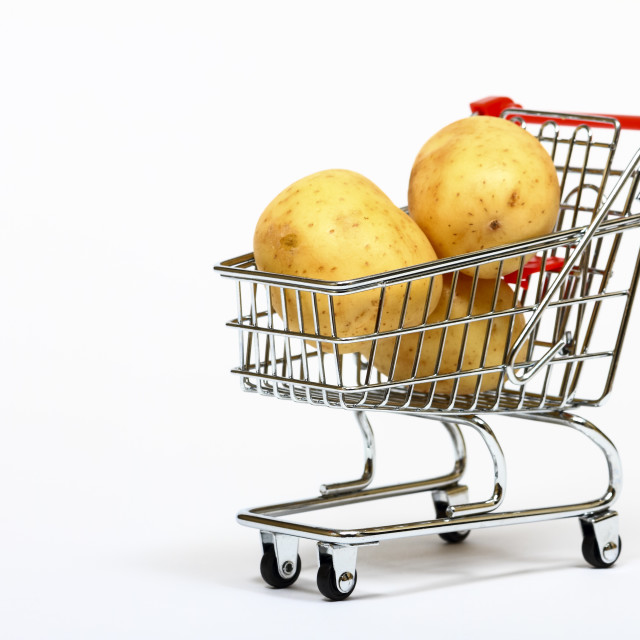 """Conceptual image of a miniature shopping trolley filled with potatoes isolated on a white background with space for copy"" stock image"