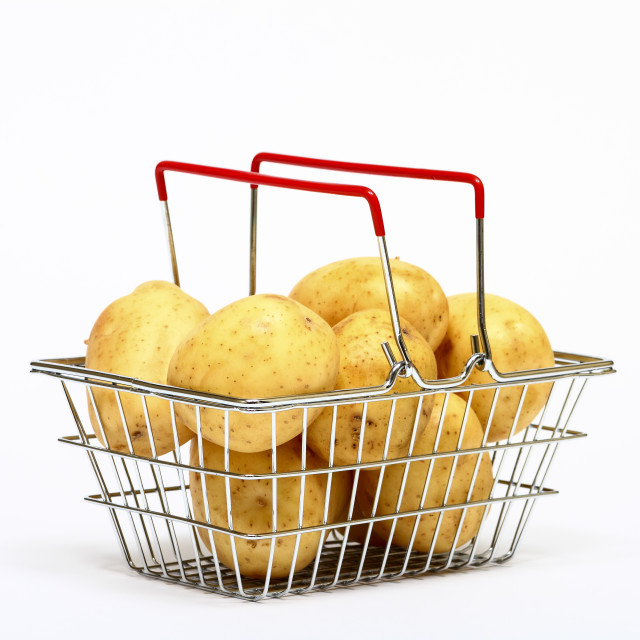 """Miniature shopping basket filled with potatoes isolated on a white background"" stock image"