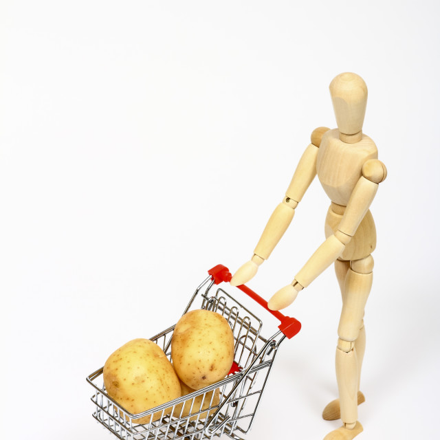 """Conceptual image of a miniature shopping trolley filled with potatoes being pushed by a manikin isolated on a white background with space for copy"" stock image"