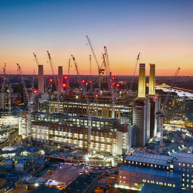 """Industrial Sunset. The bright lights of the Battersea Power Station development light up the banks of the River Thames in London."" stock image"