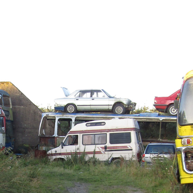 """Derelict cars and buses in field"" stock image"