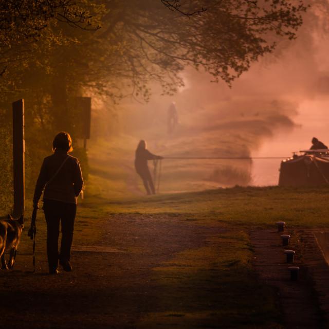 """Dog walker along canal at sunrise"" stock image"