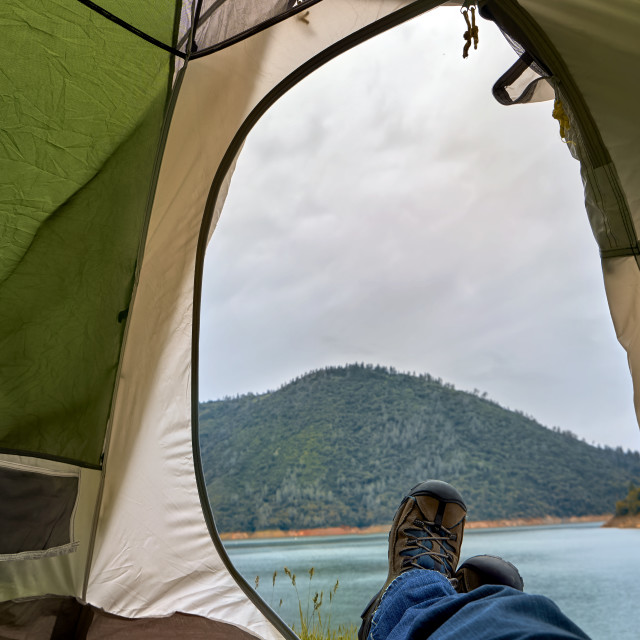 """Tent doorway view of a cloudy mountain lake landscape"" stock image"