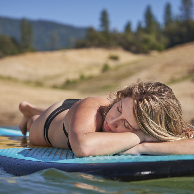 """Young Woman Resting On A Paddle Board."" stock image"
