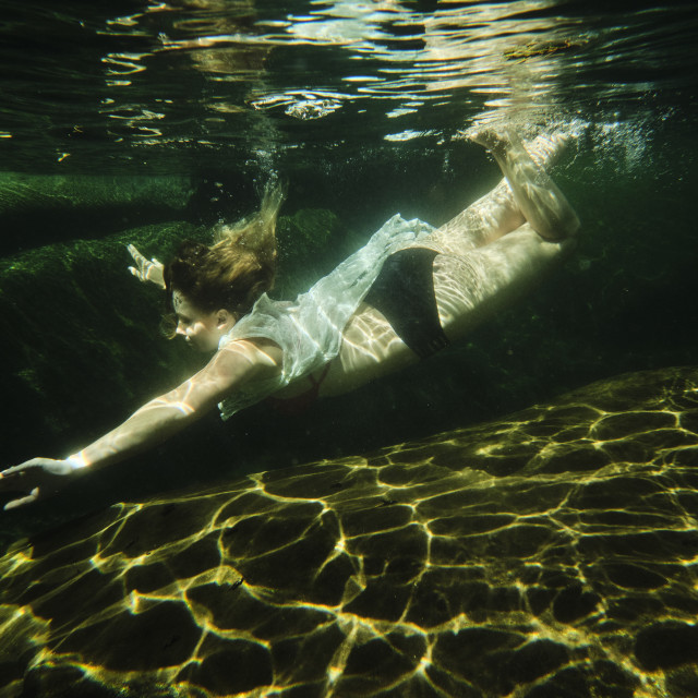 """A Young Woman Swimming Underwater In A Clear Mountain Creek on Vacation"" stock image"