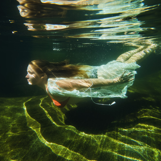 """A Young Woman Swimming Underwater in a Clear Mountain Stream."" stock image"