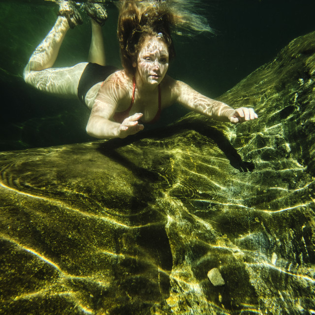 """Woman swimming underwater in a clear mountain creek."" stock image"