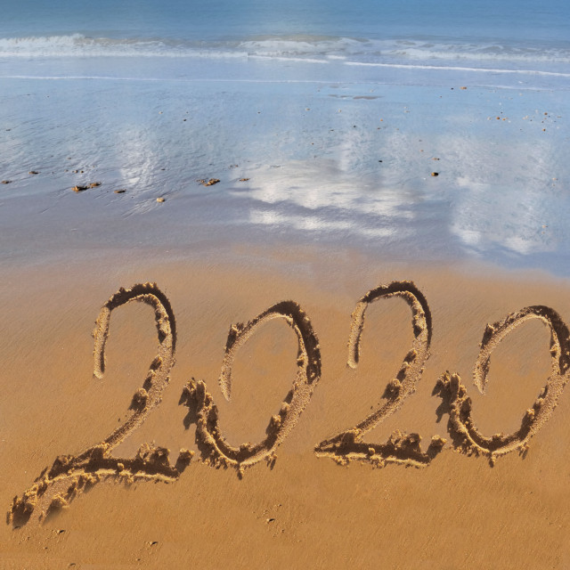"""2020 handwritting on the sand to the beach with ocean background"" stock image"