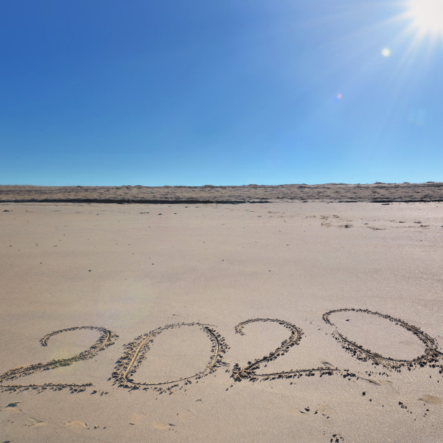 """2020 written on the sand under a beautiful sunny blue sky"" stock image"