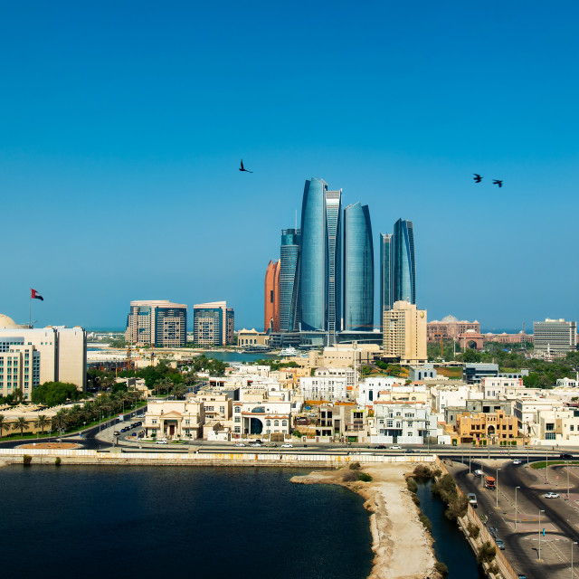 """Abu Dhabi skyline view of the downtown modern buildings rising over the water"" stock image"