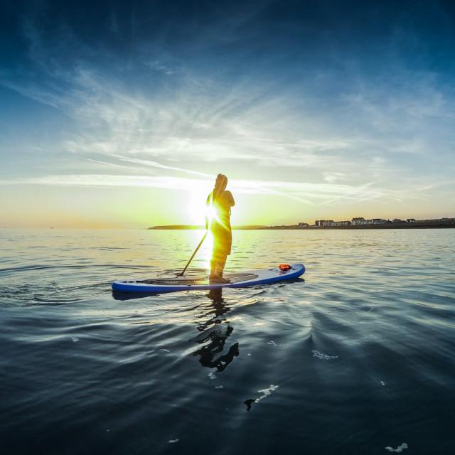 """""""Sunset paddle boarding."""" stock image"""