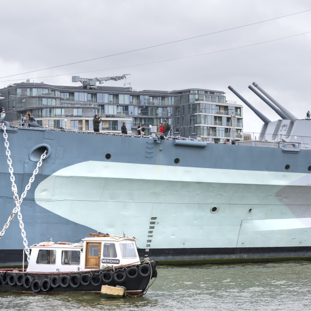 """Bow of HMS Belfast and small launch."" stock image"