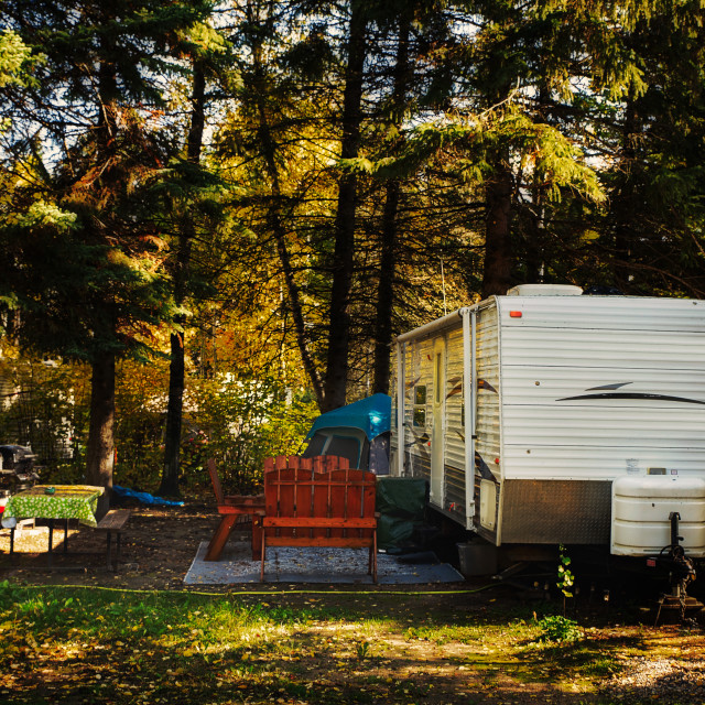 """""""A deserted camper trailer and tent with wooden chairs on outdoor carpet and cloth covered table surrounded by tall pine trees parked in a deserted campsite in a autumn daytime landscape"""" stock image"""