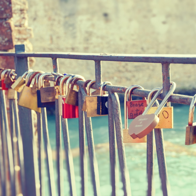 """Vintage photo of several metal locks fixed to fence in Sirmione"" stock image"