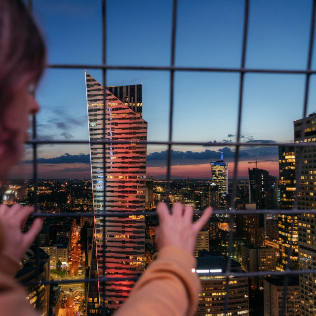 """Adult girl looks through metal grid fence at the city at night"" stock image"