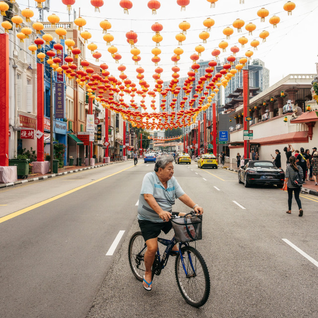 """Old man rides bike in Chinatown district, Singapore"" stock image"