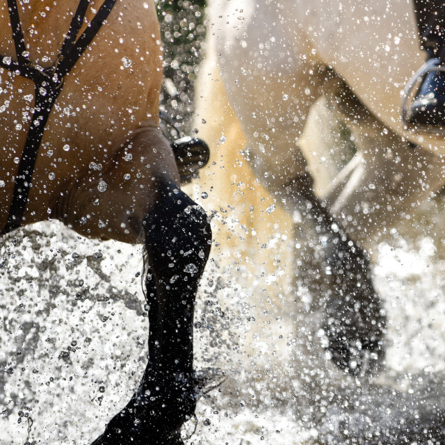 """Abstract close-up freeze frame moment as horse, ponies and riders splash through shallow river crossing at West Linton at one day equestrian event in Scottish Borders, Scotland."" stock image"