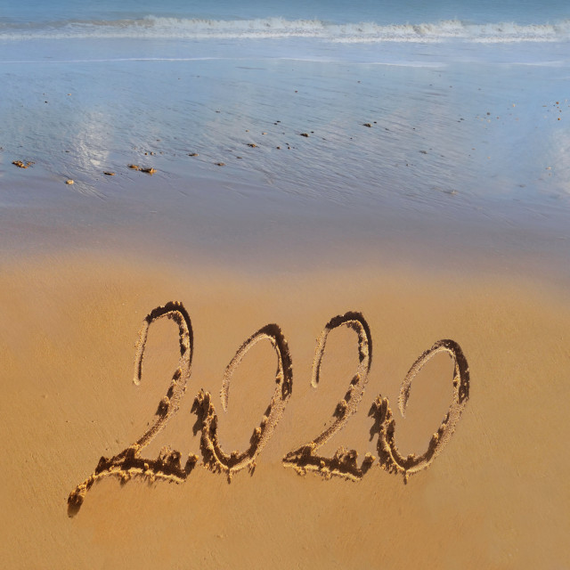 """year 2020 handwritten on the sand in front of the sea"" stock image"