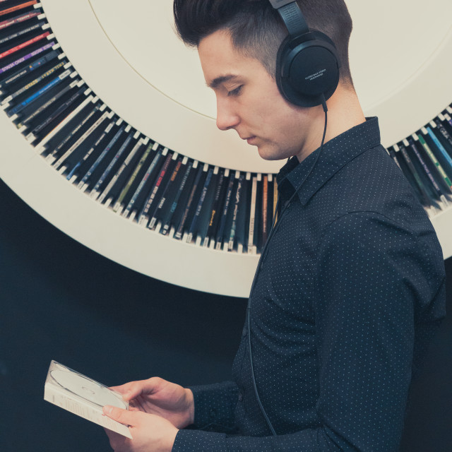 """""""Young man listening to music through headphones standing next to"""" stock image"""