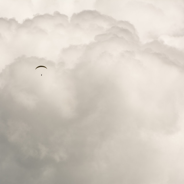 """The paragliding pilot flying towards a huge cumulonimbus"" stock image"