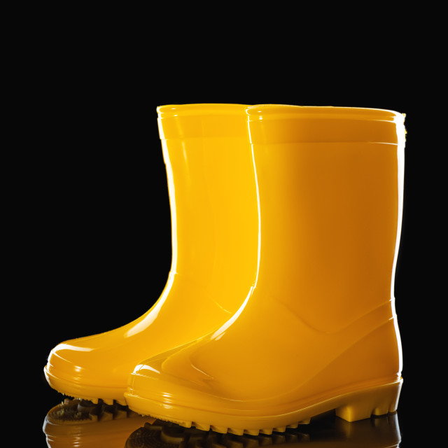 """""""Yellow Rubber Rain Boots for kids isolated on black background"""" stock image"""