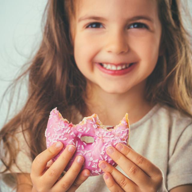 """""""Sweet little girl eating pink donut"""" stock image"""
