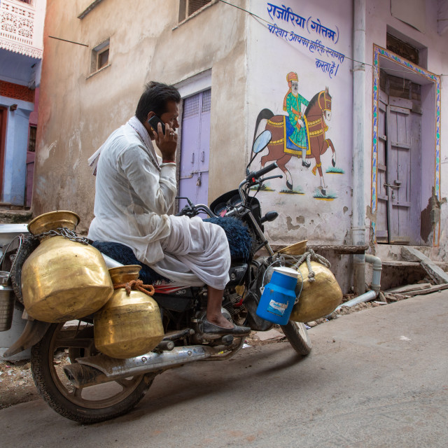 """""""Indian man calling on his phone to deliver fresh milk with his motorbike,..."""" stock image"""