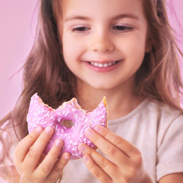 """Happy little girl eating pink donut"" stock image"
