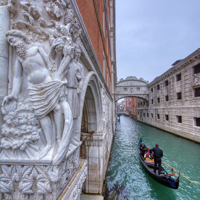 """Gondola with tourists sails on old canal under medieval Bridge of Sighs, Venice, Italy."" stock image"