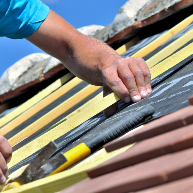 """close on the hands of a worker renoving e roof of a house"" stock image"