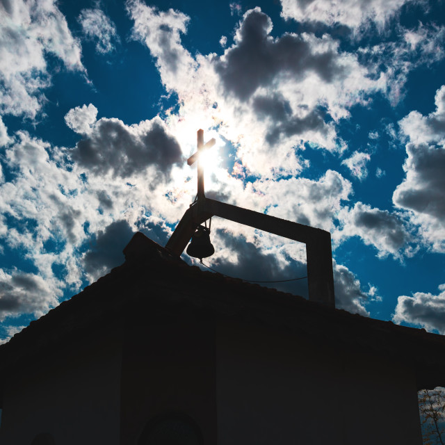 """""""Cross silhouette on the roof of the old church against sun rays"""" stock image"""