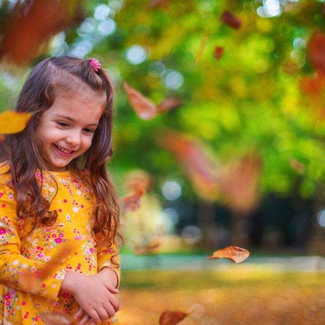 """""""Little smiling girl playing with autumn leaves in a sunshine par"""" stock image"""