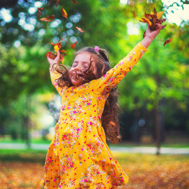 """""""Autumn park and happy little girl playing with fallen tree leave"""" stock image"""