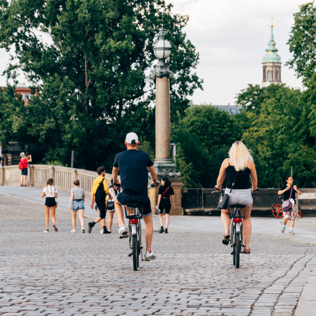 """Unidentified people riding rental bicycles on bridge in Berlin"" stock image"